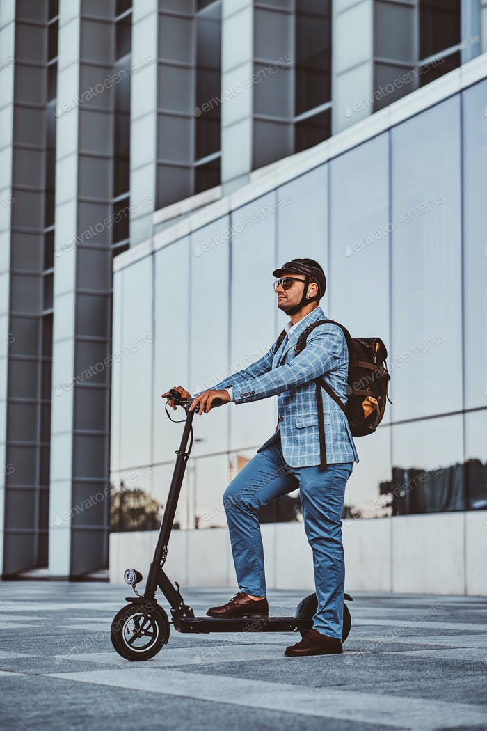 Man is driving his new electro scooter near big glass building