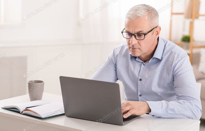 Serious senior man using laptop at home office