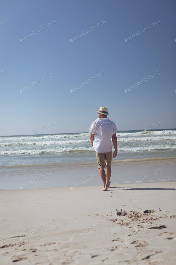 Rear view of young Caucasian man walking at beach on a sunny day. He wears a hat