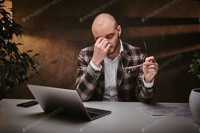 Уверенный европейский красивый бизнесмен сидит в офисе