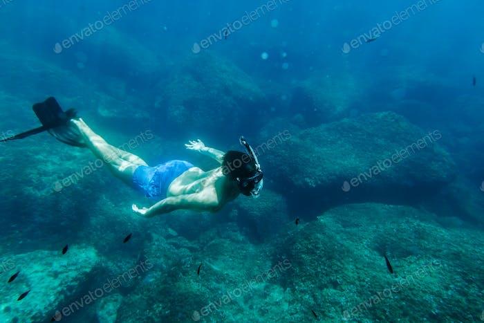 Mann schwimmen unter Wasser im Schnorchel