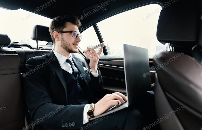 Young businessman talking on phone in taxi