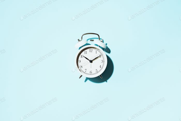 White alarm clock with hard shadow on blue background. Top view