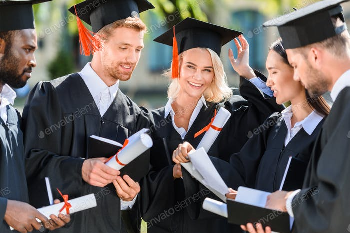 smiling multiethnic graduated students in capes with diplomas