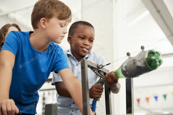 Two schoolboys using air pressure rocket at a science centre