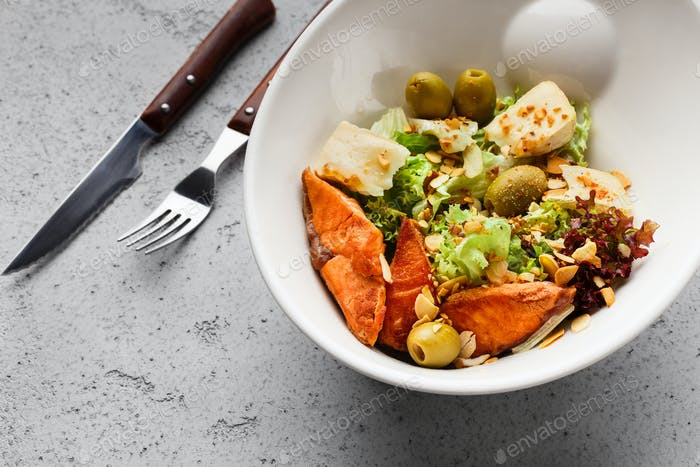 Fresh salad with salmon, olives and cheese