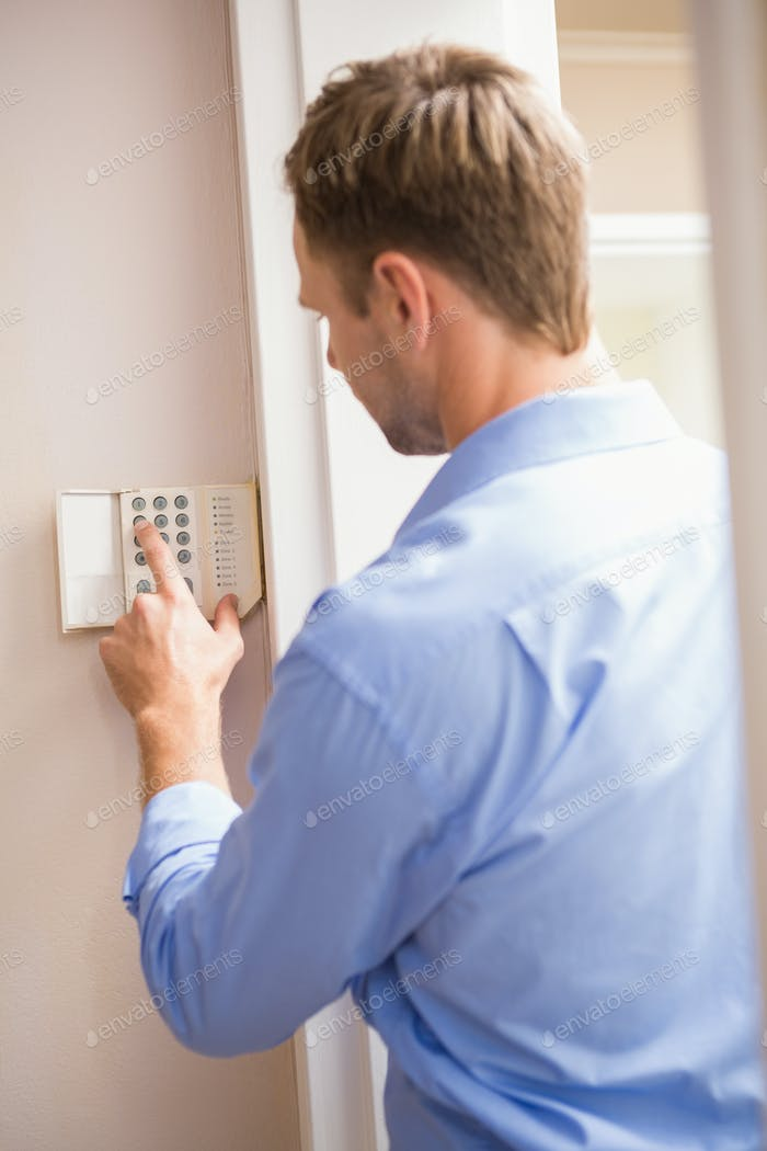 Man arming a home alarm on the wall