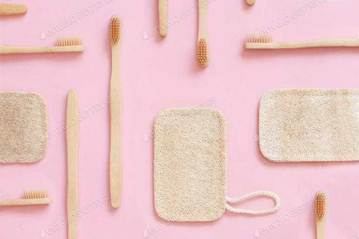 Eco friendly bamboo toothbrushes and dish washing sponges on pink background