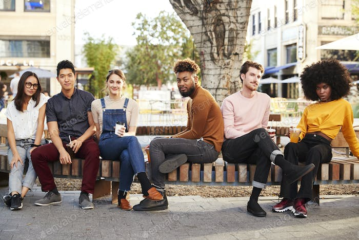 Six millennial hipster friends in the city relaxing by a fountain with drinks, smiling to camera