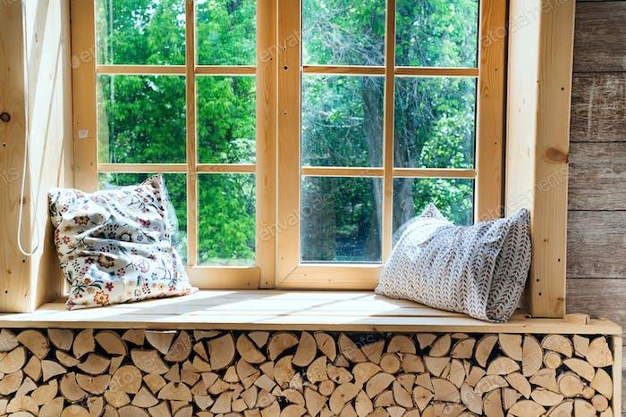Светлый интерьер комнаты с шторами, деревянными подоконниками и подушками