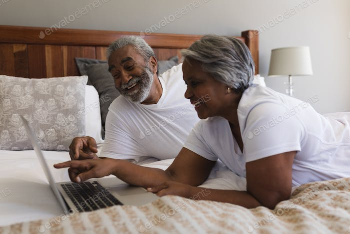 Side view of happy senior African American couple using laptop while laughing in bedroom at home