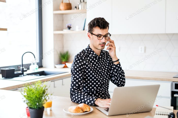 Young man with laptop and smartphone sitting in kitchen, a home office concept