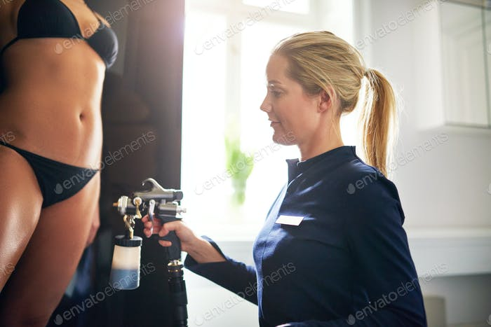 Woman spraying client with airbrush during spraytan session