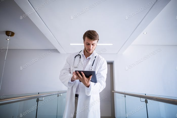 Doctor using digital tablet in corridor