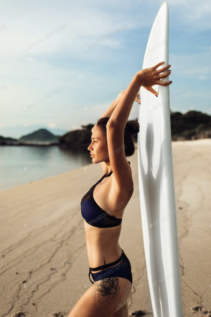 sporty attractive girl or young woman holding surfboard