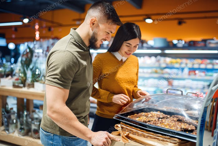 Family couple choosing cakes in grocery store