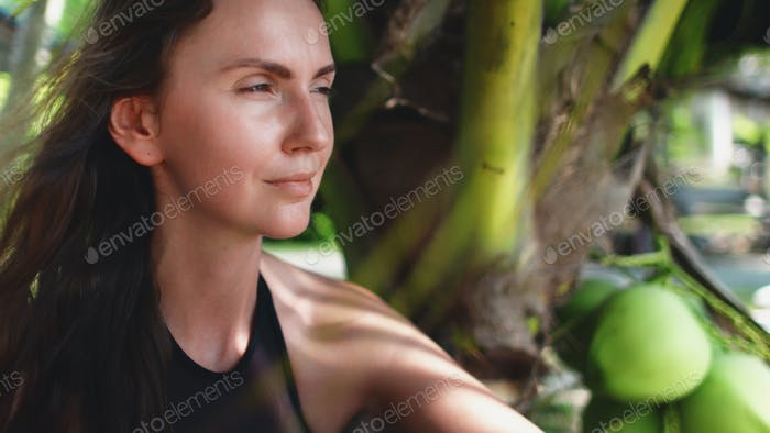 woman sitting under palm tree exotic vacation