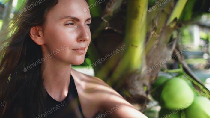 Frau sitzt unter Palme exotischen Urlaub