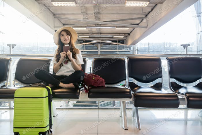 Happy Asian woman traveler holding the passport with suitcases in modern an airport,