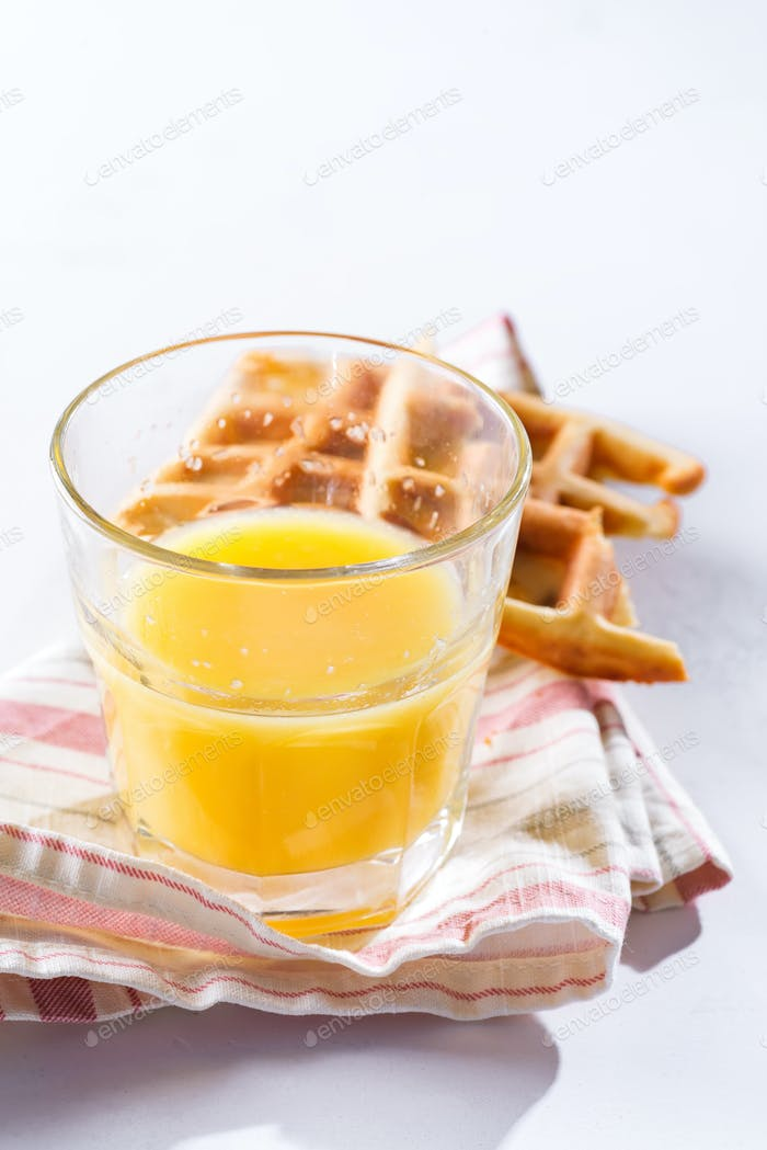 Orange juice and belgian or french waffles for breakfast on light background