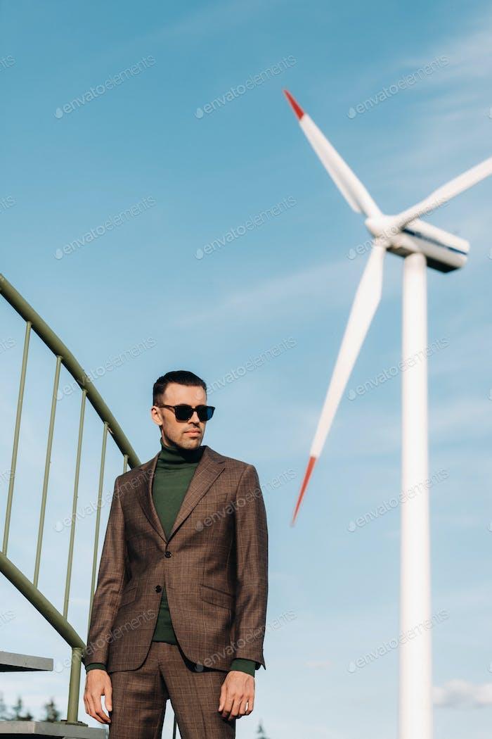 Ein Mann in einem Business-Anzug mit einem grünen Golf-Shirt steht neben einer Windmühle vor dem Hintergrund