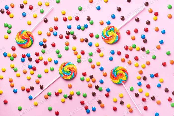 Multicolored lollipop, rainbow colorful candies on pink background. Coated chocolate sweet pieces