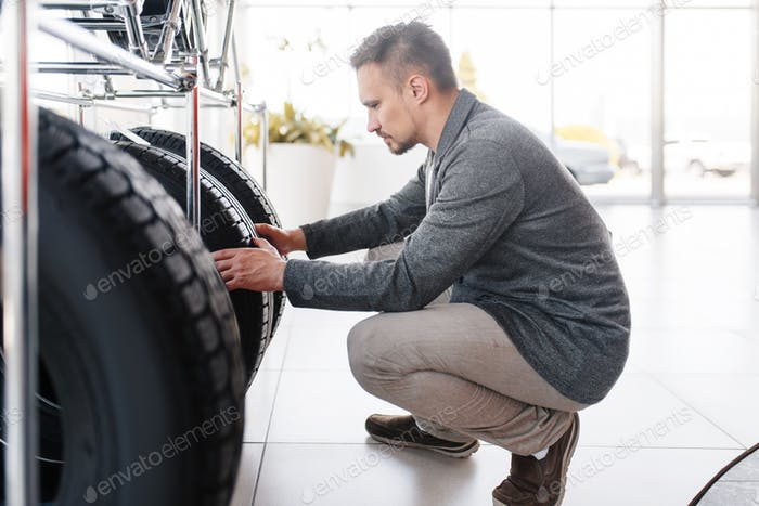 Man choosing tyres for new car in showroom