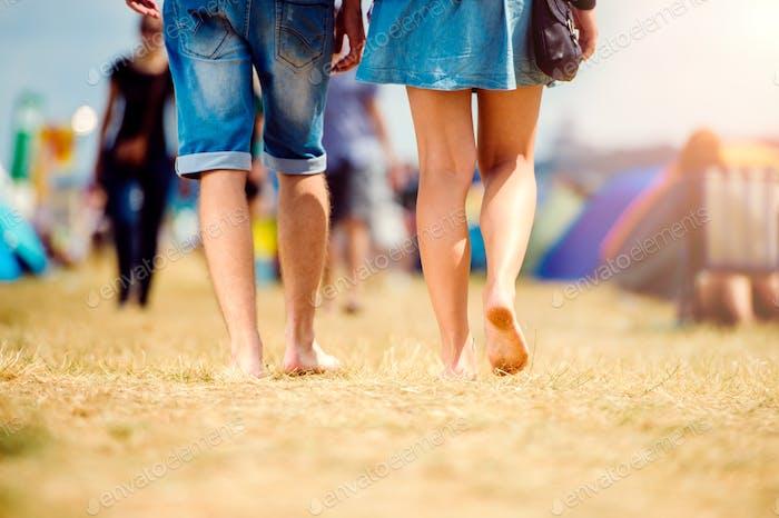 Unrecognizable teenage couple, tent festival, sunny summer, legs