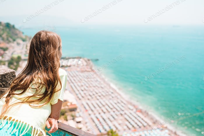 Young girl in background of mediterranean sea and sky