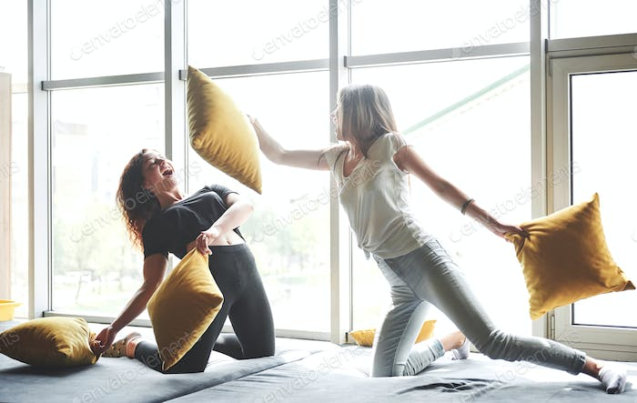 Funny girlfriends play pillows, near large windows