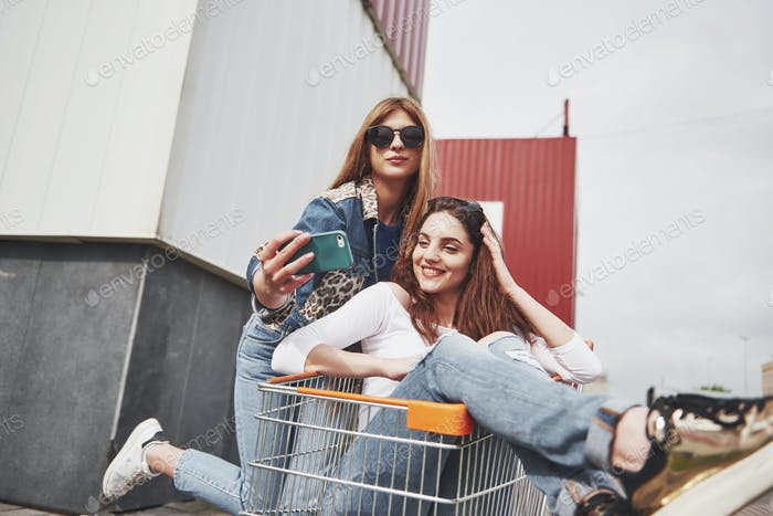 Two young happy women having fun shopping trolley race outdoors