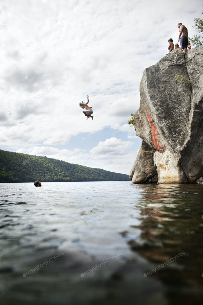 Eine Gruppe junger Leute, die aus der Höhe von einer Klippe in das stille Wasser eines Sees springen.