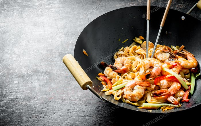 Chinese wok. Udon noodles in a wok pan with shrimp and sauce.