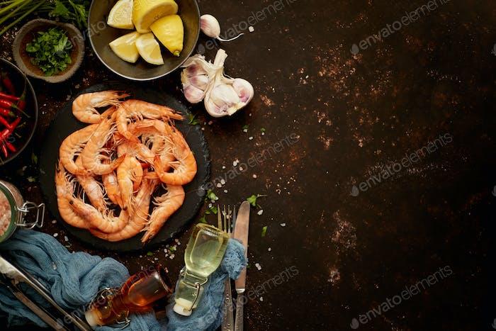 Meeresfrüchte-Zusammensetzung mit Garnelen oder Garnelen. Auf dunklem Hintergrund mit vielen Zutaten. Flache Lay