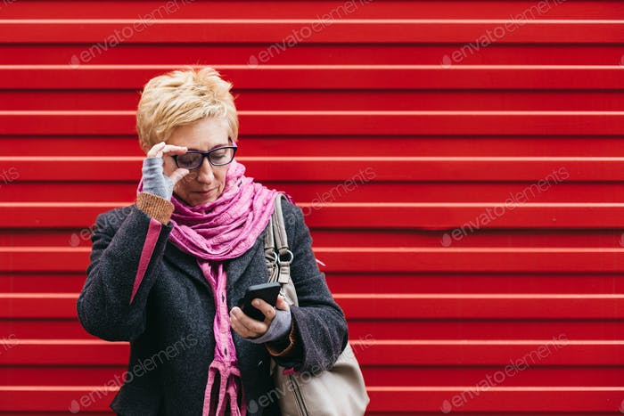 Adult woman with smartphone on street