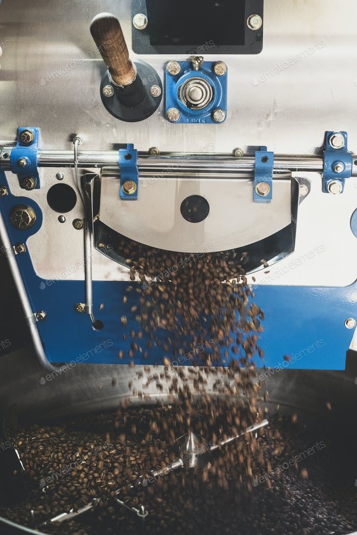 Close up of freshly roasted coffee beans pouring from coffee roaster.
