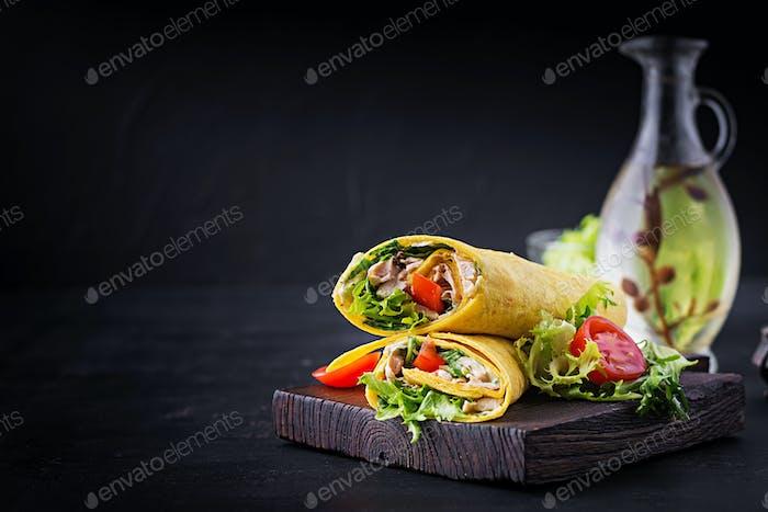 Frische Tortilla-Wraps mit Huhn und frischem Gemüse auf Holzbrett.