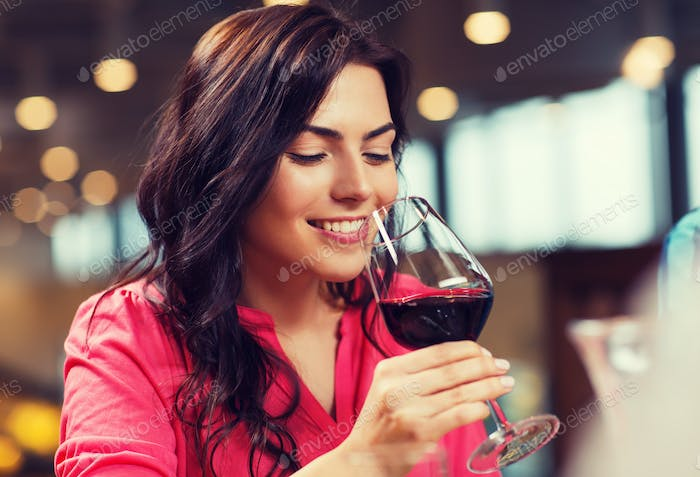 smiling woman drinking red wine at restaurant