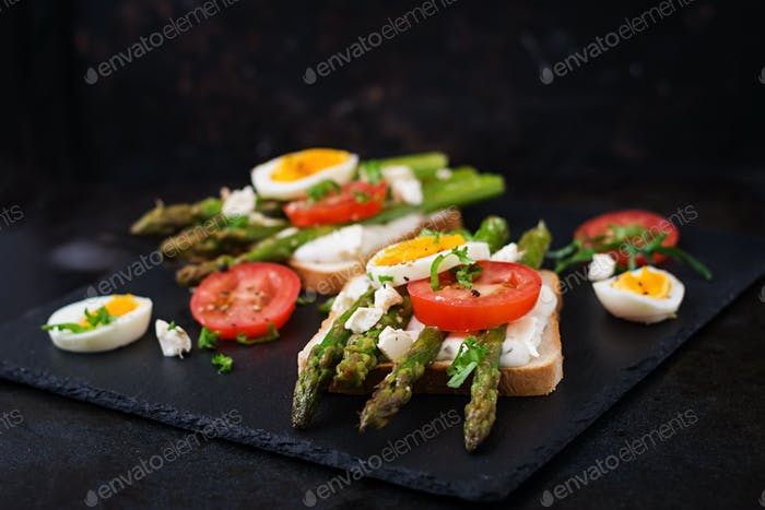 Sandwiches with caramelized asparagus, feta cheese, tomatoes and eggs.