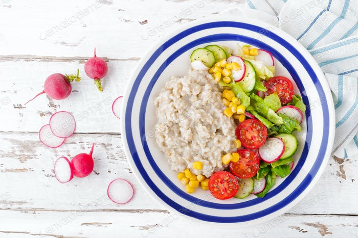 Oatmeal porridge with boiled egg and vegetable salad with fresh radish, cucumber and lettuce