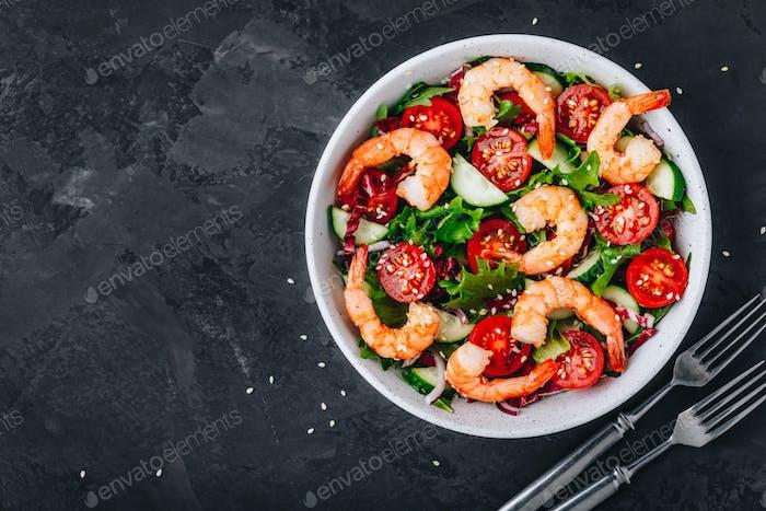 Garnelensalat mit frischem grünem Salat und Radicchio-Blättern, Gurken, Tomaten und Sesam.