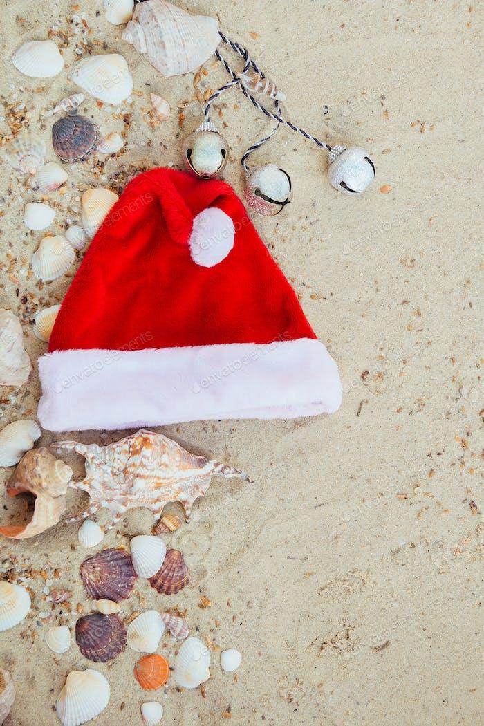 Weihnachtsmütze am Strand. Santa der Sand in der Nähe von Muscheln.Neujahr Urlaub.