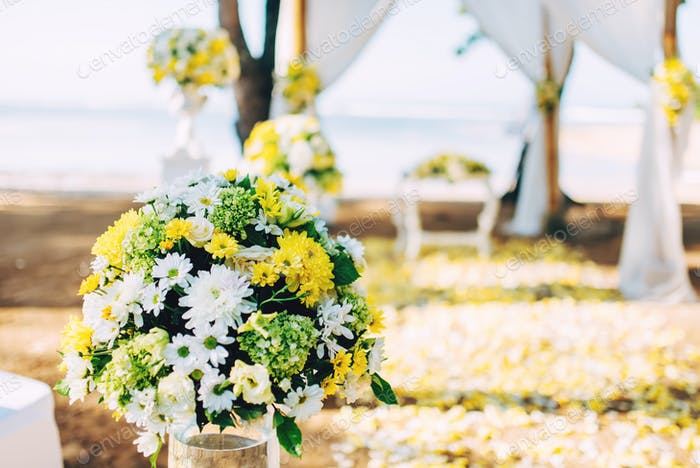 Flower decoration, details of beach wedding set up. Romantic and private ceremony of bride and groom