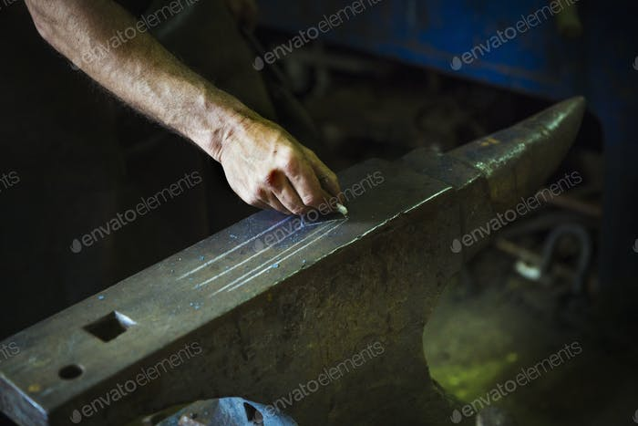 A blacksmith draws a design onto an anvil with chalk.