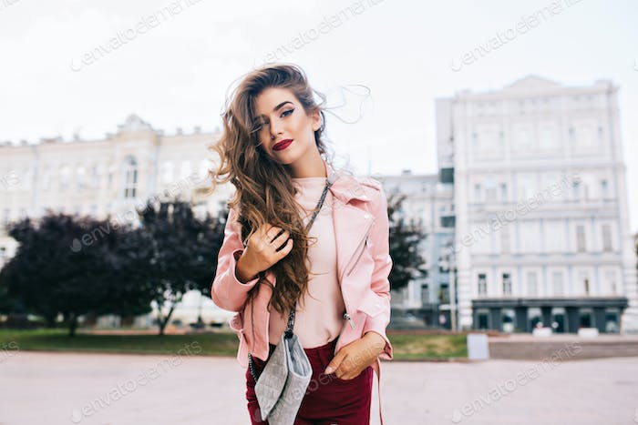 Attractive girl with long hairstyle in vinous pants is posing to camera in city.