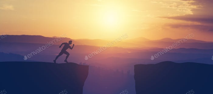 Man running towars cliff in the mountains.