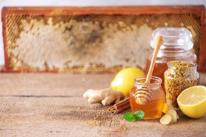 Ingredients for healthy hot drink. Lemon, ginger, mint, honey, apple and spices on wooden background