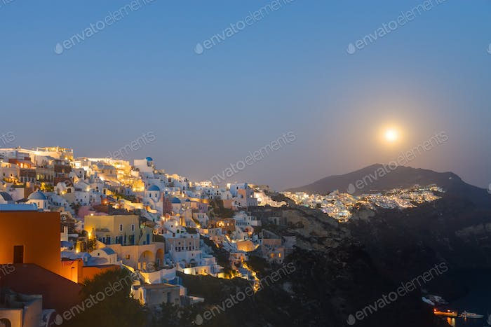 The moon rises over Oia