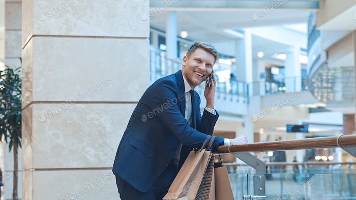 Young smiling businessman with shopping bags