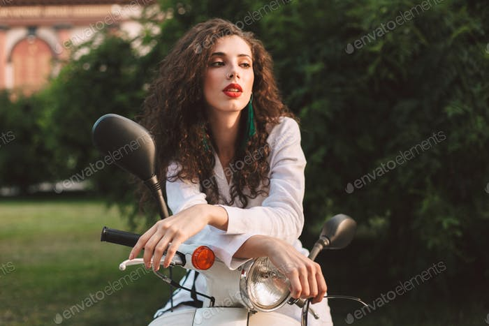 Beautiful lady in white suite leaning on scooter thoughtfully looking aside